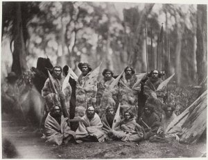 Group of Aborigines, sitting and standing, whole-length, full face, wearing animal skins, some holding weapons. Picture taken by Antoine Fauchery approx. 1857  State Library of Victoria collection
